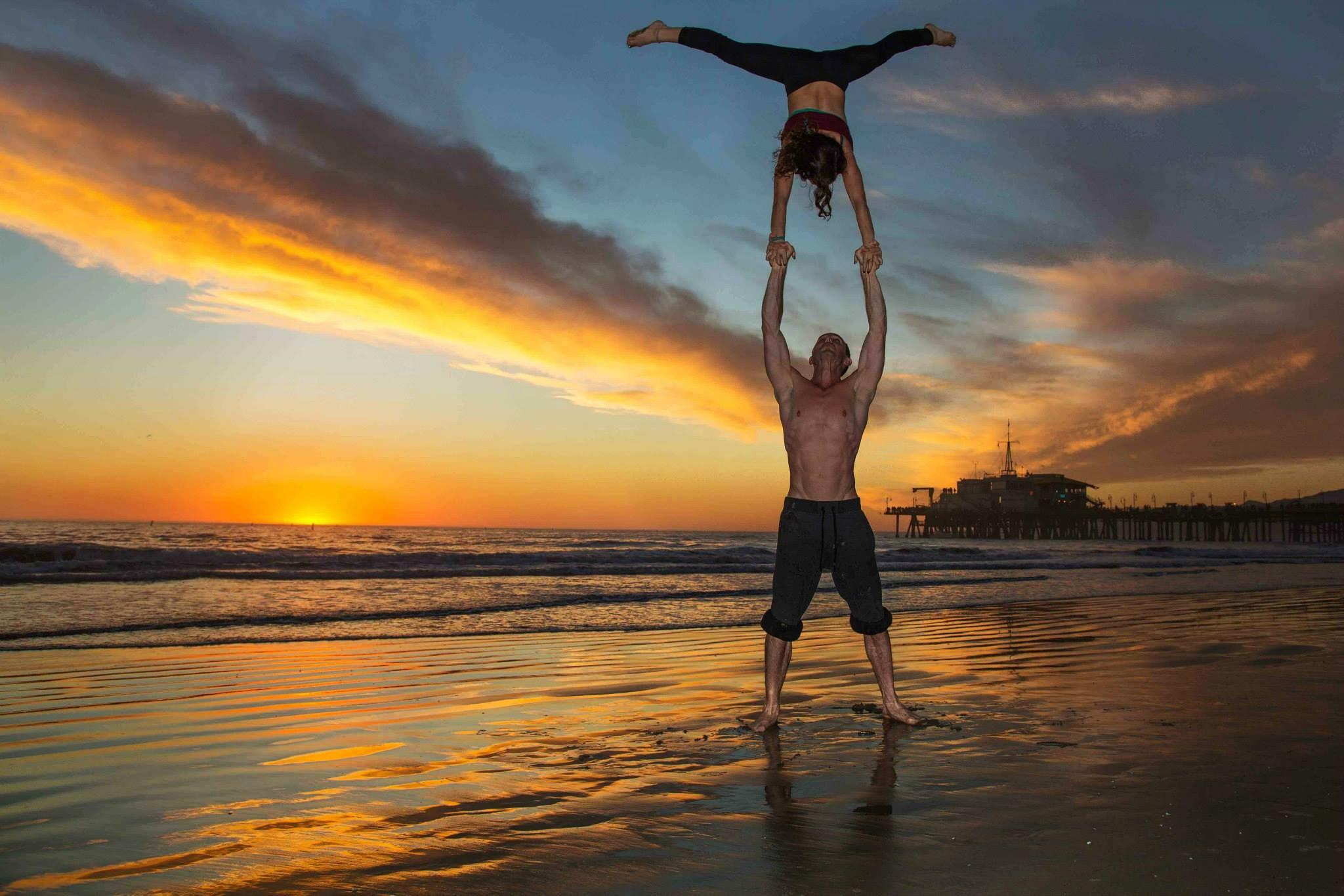 a yoga couple practicing acro-yoga