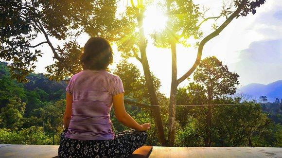 Woman sitting in meditation. www.BookMeditationRetreats.com