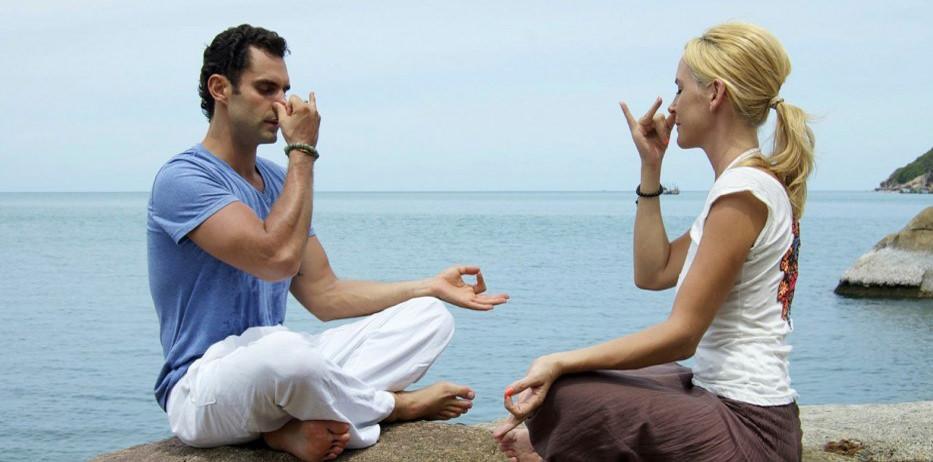 A man and a woman demonstrating anulom vilom pranayama