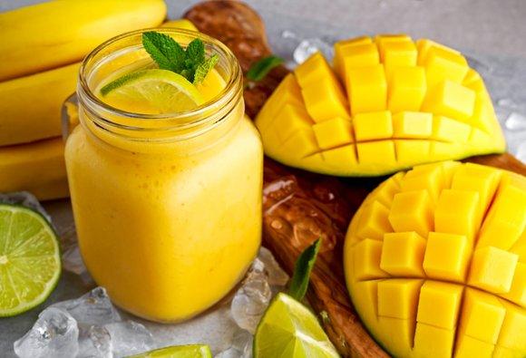 A mason jar full of mango smoothie